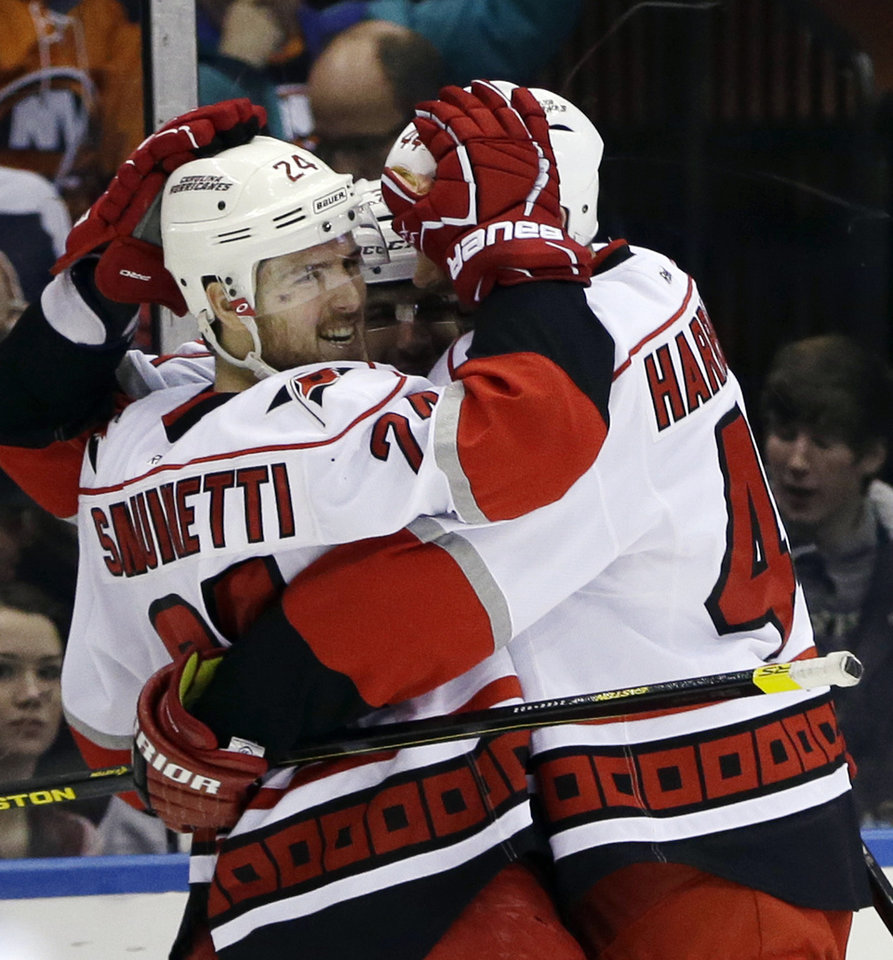 Photo - Carolina Hurricanes defensemen Bobby Sanguinetti (24) and Jay Harrison (44) celebrate with a third teammate after Sanguinetti scored the go-ahead goal against the New York Islanders in the third period of their NHL hockey game at Nassau Coliseum in Uniondale, N.Y., Sunday, Feb. 24, 2013. The Hurricanes won 4-2. (AP Photo/Kathy Willens)