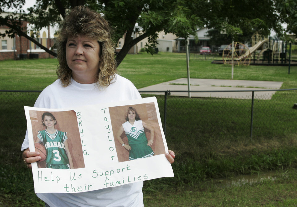 Photo -  Dena Priddy holds a sign with photos of the two Weeletka girls, 13-year-old Taylor Paschal-Placker, right,  and 11-year-old Skyla Whitaker who were murdered Sunday, as she collected donations for the families outside Graham Public School in Weleetka, Okla., Tuesday, June 10, 2008. (AP Photo)