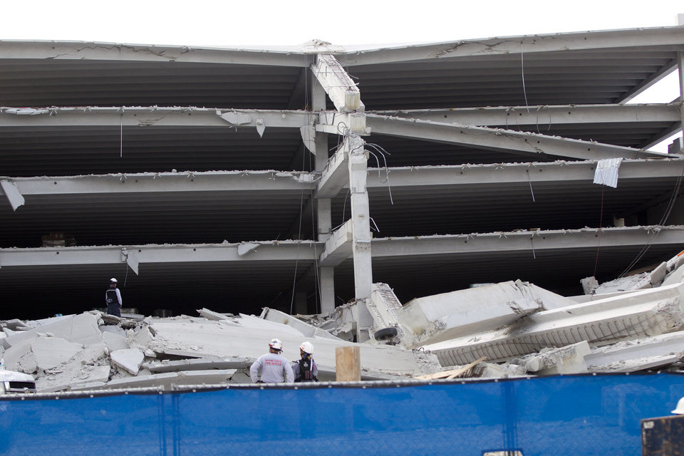 Fire Rescue officials search for victims trapped in the collapsed parking garage at the Miami Dade College West campus in Doral, Fla. Tuesday, Oct. 10, 2012 . (AP Photo/J Pat Carter)