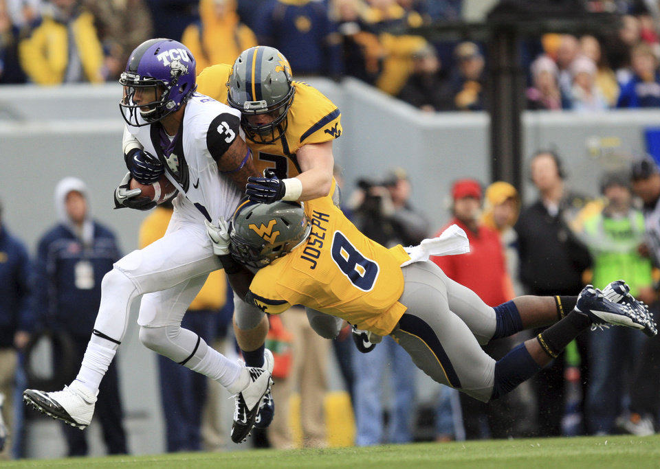 Photo -   West Virginia's Jared Barber (33) and Karl Joseph (8) tackle TCU's Brandon Carter (3) during the first half of their NCAA college football game in Morgantown, W.Va., on Saturday, Nov. 3, 2012. (AP Photo/Christopher Jackson)