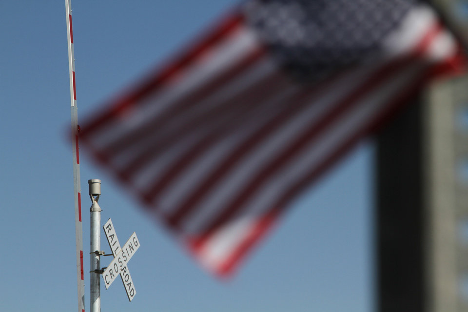 Photo -   A flag flies at the scene of an accident where four veterans were killed and 16 other people were injured when a train slammed into a parade float carrying the returning heroes to a banquet last Thursday in Midland, Texas on Saturday, Nov. 17, 2012. Federal investigators were trying to determine whether the two-float parade had been given enough warning to clear the tracks. (AP Photo/Juan Carlos Llorca)