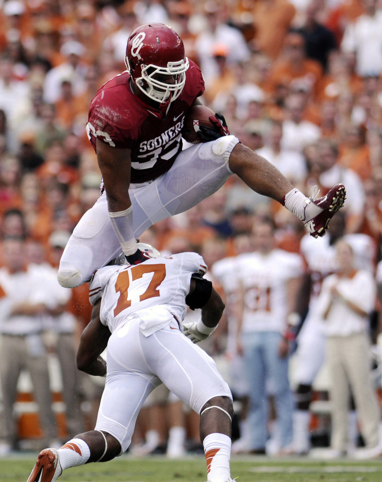 Photo -   Oklahoma fullback Trey Millard hurdles Texas saferty Adrian Phillips during the first quarter of an NCAA college football game at the Cotton Bowl Saturday, Oct. 13, 2012, in Dallas. (AP Photo/The Daily Texan, Lawrence Peart)