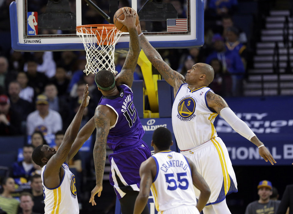Photo - Golden State Warriors forward Marreese Speights (5) blocks a dunk attempt from Sacramento Kings center DeMarcus Cousins (15) during the second half of an NBA basketball game on Friday, April 4, 2014, in Oakland, Calif. Golden State won 102-69. (AP Photo/Marcio Jose Sanchez)
