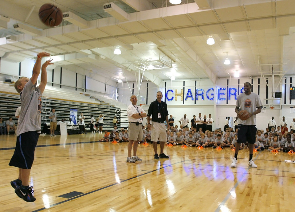 Photo - Kevin Durant goes head-to-head in a shootout with Jake Cochnauer, 8 of Minnesota, during the second day of the Kevin Durant basketball camp at Heritage Hall in Oklahoma City, Thursday, June 30, 2011.  Photo by Garett Fisbeck, The Oklahoman