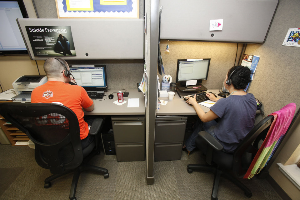 Photo - Call specialists work the telephones at the Lifeline suicide prevention hotline number in Oklahoma City.