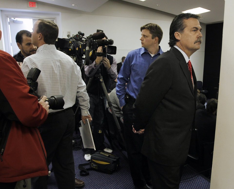 Photo -   Former Tennessee Titans head coach Jeff Fisher, right, waits to walk to the podium to address the media during an NFL football news conference at the team's headquarters on Friday, Jan. 28, 2011, in Nashville, Tenn. The Titans announced on Thursday that Fisher will not remain as head coach. (AP Photo/Mark Humphrey)