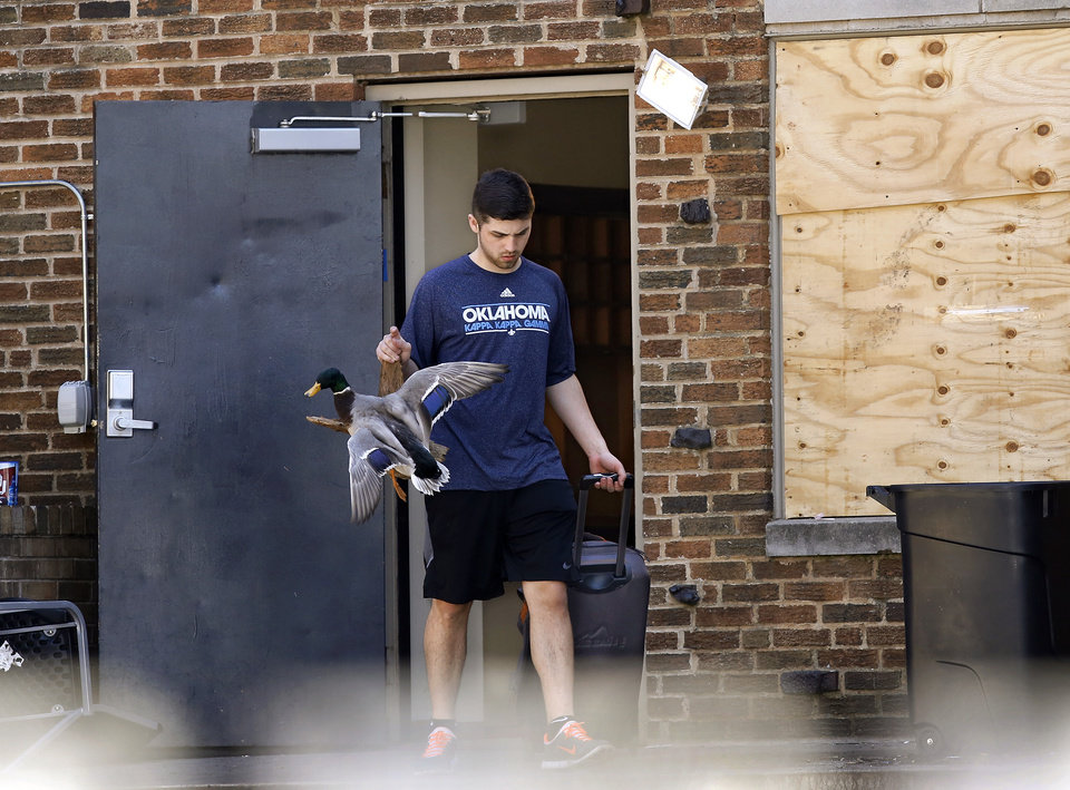 Photo - Parents, friends and fellow students helped members of the SAE  fraternity remove all furniture and personal belongings from the house Tuesday afternoon, March 10, 2015. University officials closed the house and ordered it to be vacated by Tuesday night after a video showing students affiliated with the fraternity uttering offensive racial slurs during a weekend outing.      Photo by Jim Beckel, The Oklahoman