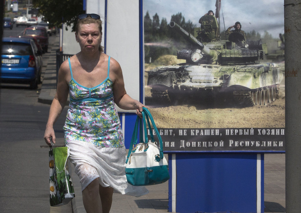 Photo - A woman walks past a poster calling for military recruits to the separatist forces in the city of Donetsk, eastern Ukraine Monday, Aug. 4, 2014.  The Interfax news agency reported Monday that Russia's air force began week-long military drills in the central and western regions of Russia, a move that could spark further fears that Moscow is ready to flex its military muscle in Ukraine. (AP Photo/Dmitry Lovetsky)
