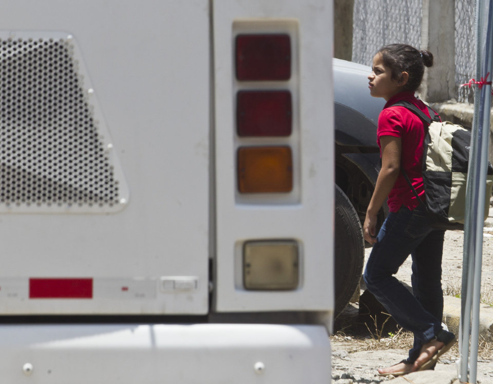 Photo - A girl, deported from the United States, walks to board a bus that will take her to the Center for Migrants Returned, upon her arrival at the airport in San Pedro Sula, Honduras, Friday, July 18, 2014. (AP Photo/Esteban Felix)