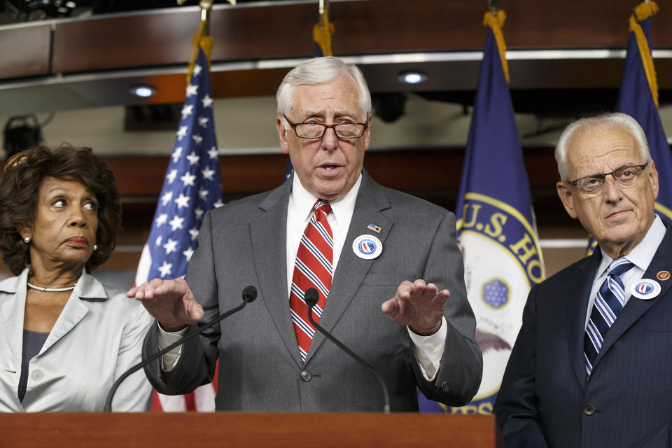 House Minority Whip Steny Hoyer of Md., joined by Rep. Maxine Waters, D-Calif., left, and Rep. Kerry Bentivolio, R-Mich., criticizes the efforts of Republicans to muscle legislation through the House authorizing an election-year lawsuit against President Barack Obama that accuses him of exceeding his powers in enforcing his health care law, Wednesday, July 30, 2014, during a news conference on Capitol Hill in Washington. Democrats have branded the effort a political charade aimed at stirring up Republican voters for the fall congressional elections. They say it's also an effort by top Republicans to mollify conservatives who want Obama to be impeached — something House Speaker John Boehner of Ohio, said Tuesday he has no plans to do.  (AP Photo/J. Scott Applewhite)