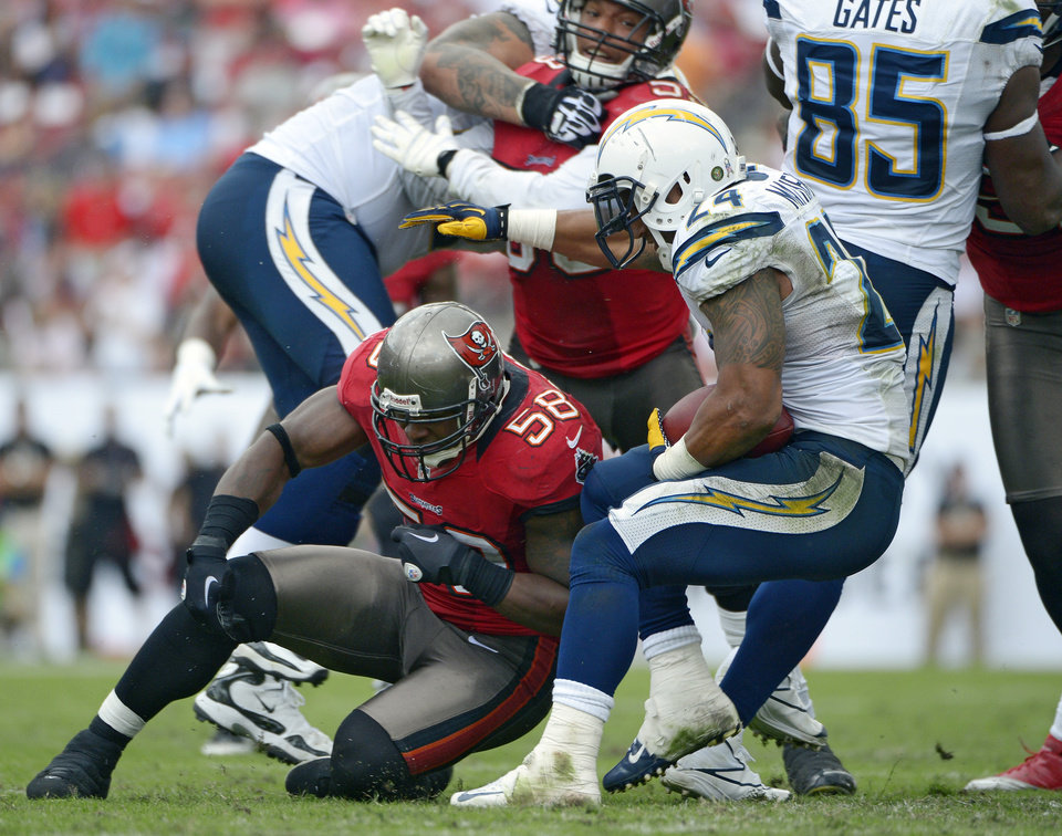 Photo -   Tampa Bay Buccaneers outside linebacker Quincy Black (58) goes down after running into San Diego Chargers running back Ryan Mathews (24) during the third quarter of an NFL football game Sunday, Nov. 11, 2012, in Tampa, Fla. Black left the game on a stretcher. (AP Photo/Phelan Ebenhack)