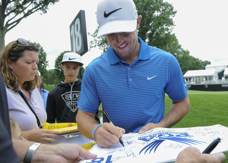 Photo - Rory McIlroy, of Northern Ireland, signs autographs after finishing his practice round at the World Golf Championships Bridgestone Invitational, Tuesday, July 29, 2014, in Akron, Ohio. (AP Photo/Phil Long)