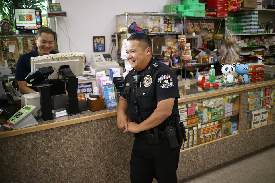 Photo -  Oklahoma County sheriff's deputy Tom Ly, with the Community Services Division, talks with Ba T. Luong while making a stop at Super Cao Nguyen market.