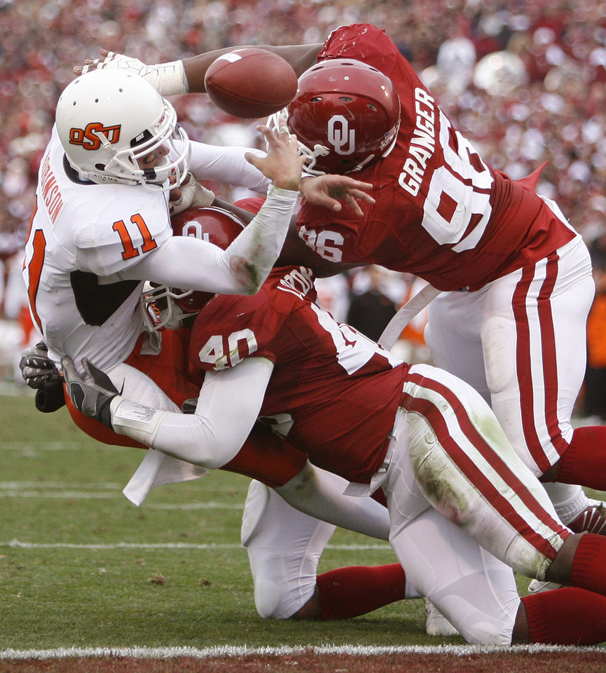 Photo - Oklahoma State's Zac Robinson (11) fumbles the ball as he is brought down by Oklahoma's Curtis Lofton (40) and DeMarcus Granger (96) on a fourth down play during the first half of the college football game between the University of Oklahoma Sooners (OU) and the Oklahoma State University Cowboys (OSU) at the Gaylord Family-Memorial Stadium on Saturday, Nov. 24, 2007, in Norman, Okla.  Photo By Bryan Terry, The Oklahoman