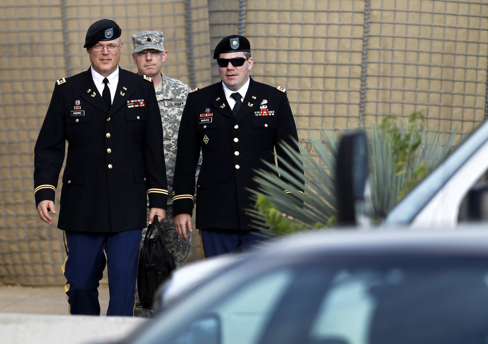Photo - From left, members of the defense, U.S. Army Lt. Col. Kris R. Poppe, Maj. Christopher E. Martin and Maj. Joseph T. Marcee, depart the Lawrence H. Williams Judicial Center, Thursday, Aug. 22, 2013, in Fort Hood, Texas. Military jurors haven't reached a verdict against the soldier on trial for the 2009 shooting rampage at Fort Hood. (AP Photo/Tony Gutierrez)