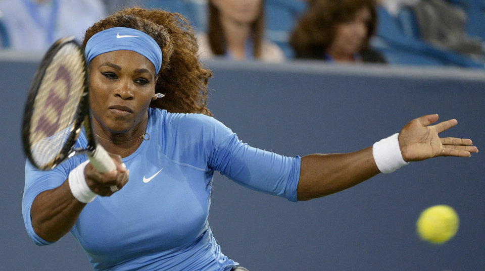 Photo - Serena Williams, from the United States, hits a forehand to Mona Barthel, from Germany, at the Western & Southern Open tennis tournament, Thursday, Aug. 15, 2013, in Mason, Ohio. (AP Photo/Michael E. Keating)