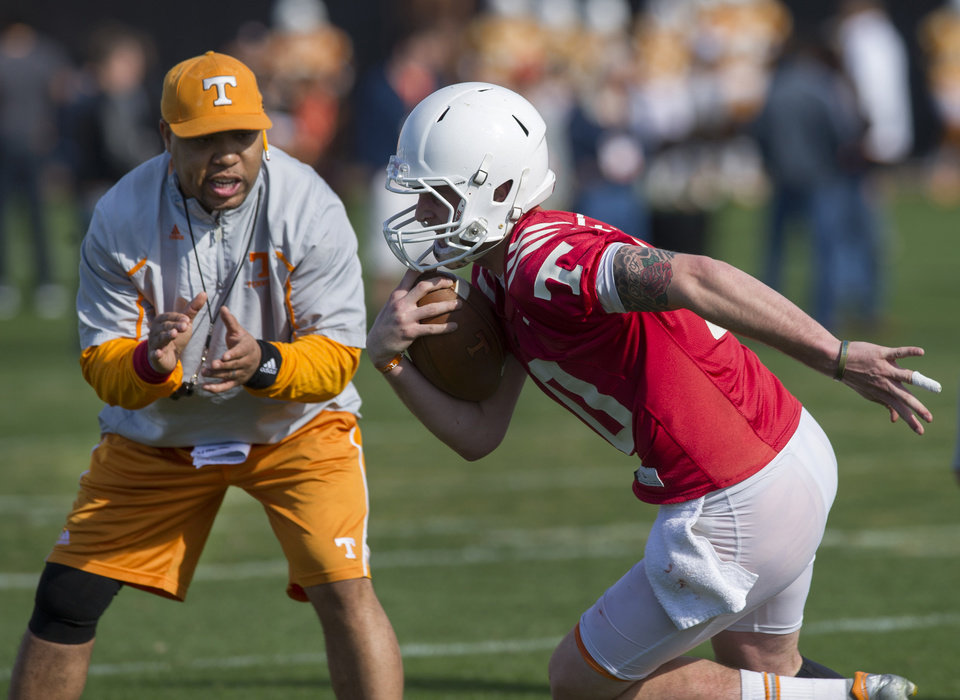 Photo - In this March 8, 2014 photo, Tennessee quarterback Riley Ferguson, right, is encouraged by running backs coach Robert Gillespie during an NCAA college spring football practice in Knoxville, Tenn. Tennessee coach Butch Jones is still waiting for someone to separate themselves from the rest in the Volunteers' four-man quarterback competition as spring practice draws to a close. (AP Photo/The Knoxville News Sentinel, Paul Efird)