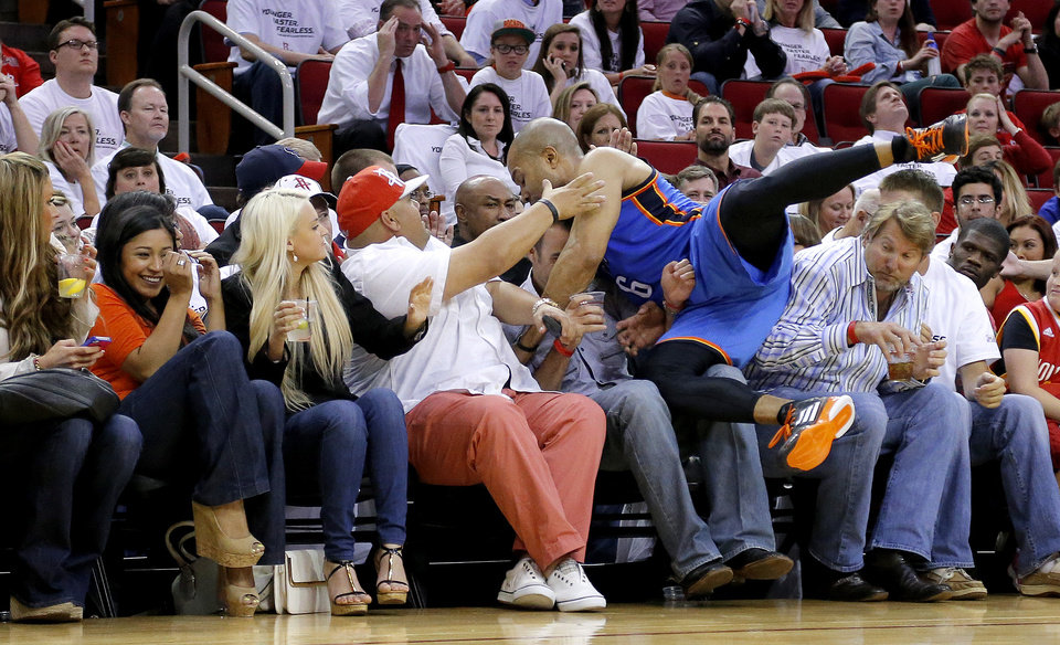 Photo - Oklahoma City's Derek Fisher (6) leaps into the crowd as he chases the ball during Game 3 in the first round of the NBA playoffs between the Oklahoma City Thunder and the Houston Rockets at the Toyota Center in Houston, Texas, Sat., April 27, 2013. Oklahoma City won 104-101. Photo by Bryan Terry, The Oklahoman