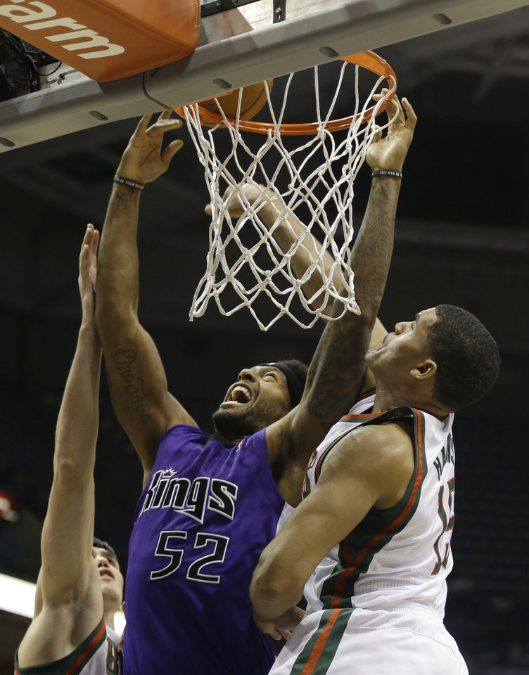 Sacramento Kings' James Johnson (52) shoots against Milwaukee Bucks' Ersan Ilyasova, left, and Tobias Harris during the first half of an NBA basketball game on Wednesday, Dec. 12, 2012, in Milwaukee. (AP Photo/Jeffrey Phelps)