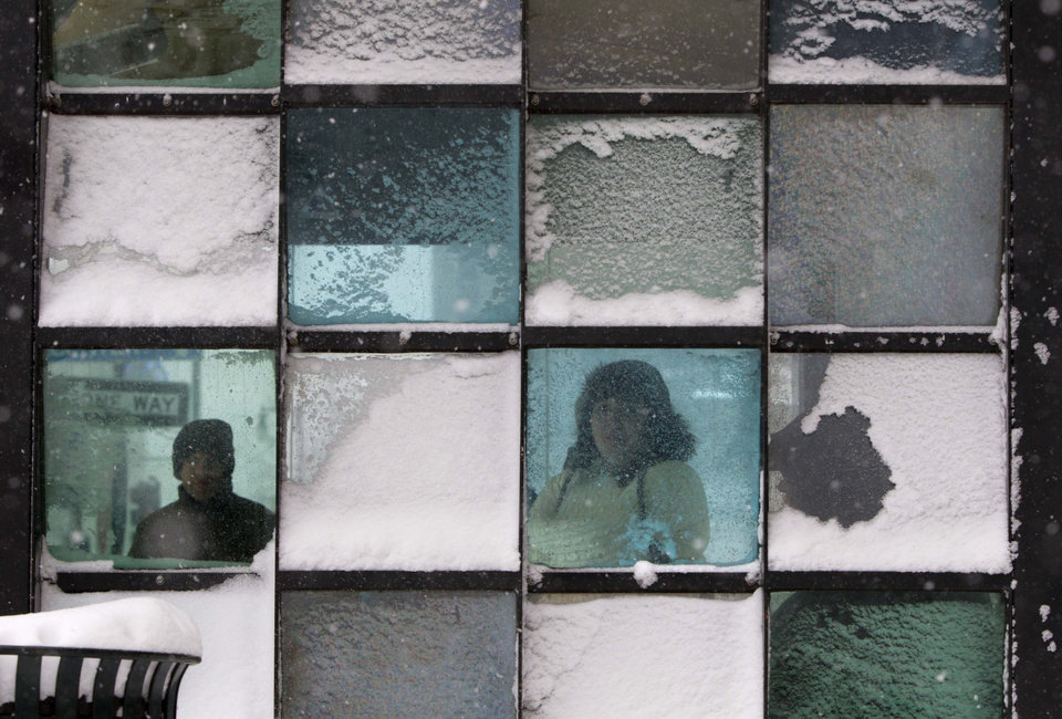 Riders wait in a bus stop where color-tinted windows collect snow during a storm, Friday, Feb. 8, 2013, in Portland, Maine. The National Weather Service says a blizzard warning is issued Friday evening for the southern coast. The forecast calls for up to 2 feet of snow and winds gusting to 50 mph.(AP Photo/Robert F. Bukaty) ORG XMIT: MERB104