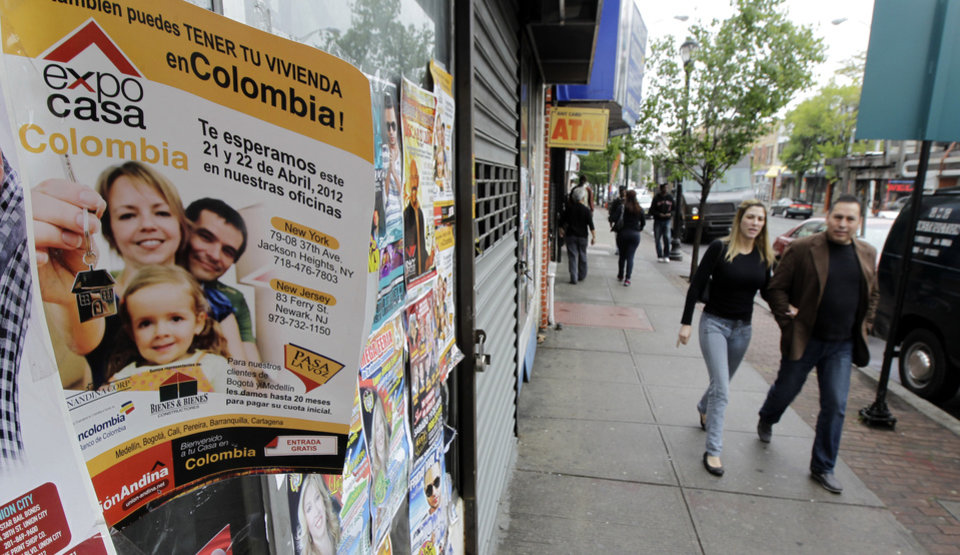 Photo -   A sign promoting an event for Colombian nationals living in the U.S. looking to buy homes hangs on the street as pedestrians walk by in Elizabeth, N.J., Tuesday, May 1, 2012. An information fair being hosted in New York this week by the Colombian government is aimed to for nationals to invest back home. (AP Photo/Julio Cortez)