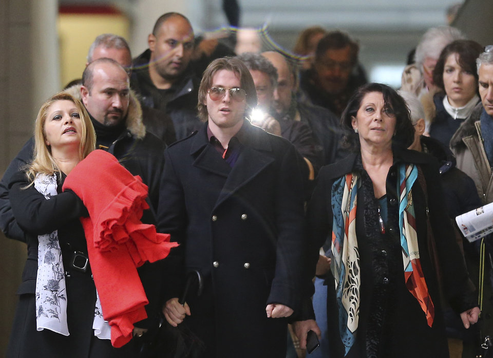 Photo - Raffaele Sollecito is flanked by his stepmother Mara Papagni, left, and his aunt Sara Achille, right, as he leaves after attending the final hearing before the third court verdict for the murder of British student Meredith Kercher, in Florence, Italy, Thursday, Jan. 30, 2014. The first two trials produced flip-flop verdicts of guilty then innocent for Kercher former roommate, American student Amanda Knox, who is not attending the hearing,  and her former Italian boyfriend, Raffaele Sollecito, and the case has produced harshly clashing versions of events. A Florence appeals panel designated by Italy's supreme court to address issues it raised about the acquittal is set to deliberate Thursday, with a verdict expected later in the day. (AP Photo/Antonio Calanni)