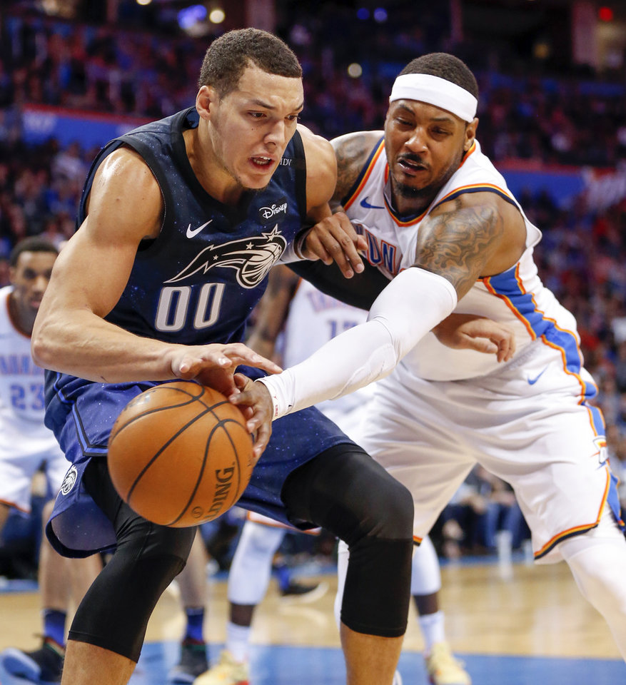 Photo - Oklahoma City's Carmelo Anthony (7) tries to steal the ball from Orlando's Aaron Gordon (00) during an NBA basketball game between the Oklahoma City Thunder and the Orlando Magic at Chesapeake Energy Arena in Oklahoma City, Monday, Feb. 26, 2018. Oklahoma City won 112-105. Photo by Nate Billings, The Oklahoman