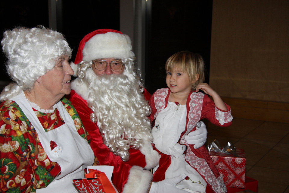 Gabrielle Davis visits with Santa and Mrs. Claus at Michael Martin Murphey\'s annual Cowboy Christmas Ball at the National Cowboy & Western Heritage Museum. Photo provided.