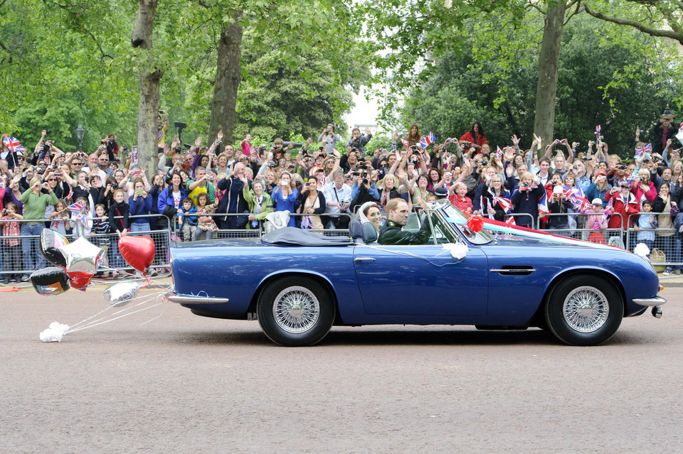 Photo - Britain's Prince William drives his wife, Kate, Duchess of Cambridge on The Mall in London in his father Prince Charles' Aston Martin Volante sports car covered with bunting on their way to Clarence House after their wedding in nearby Westminster Abbey, in London Friday April 29, 2011. (AP Photo/Jonathan Short) ORG XMIT: RWAJP139