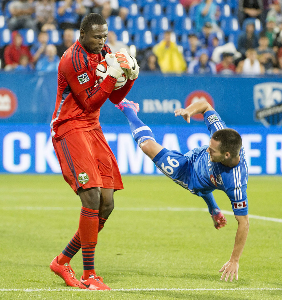 Photo - Montreal Impact Jack McInerney, right, bounces off of Portland Timbers goalie Donovan Ricketts as Ricketts makes a save during the first half of an MLS soccer game Sunday, July 27, 2014, in Montreal. (AP Photo/The Canadian Press, Peter McCabe)