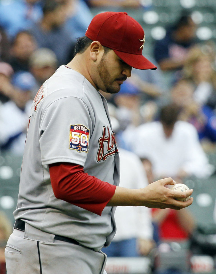Houston Astros starting pitcher Edgar Gonzalez returns to the mound after walking in a run during the fourth inning of a baseball game against the Chicago Cubs, Wednesday, Oct. 3 2012, in Chicago. (AP Photo/Charles Rex Arbogast)