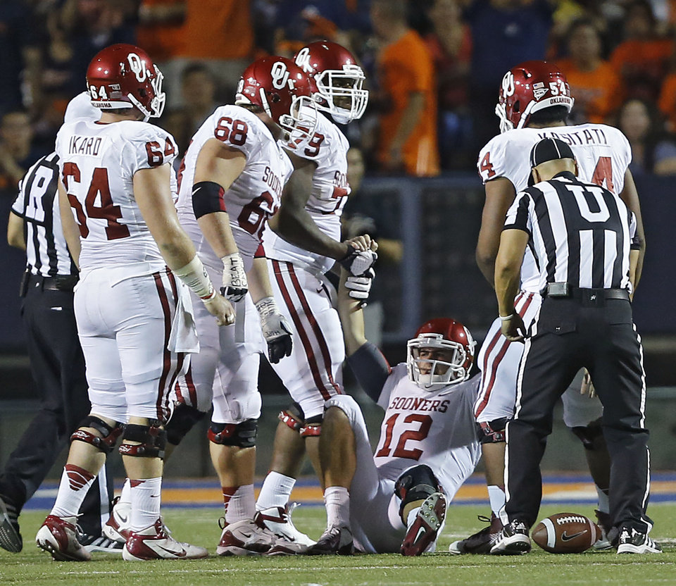 Photo - The Oklahoma offensive line helps Oklahoma Sooners quarterback Landry Jones (12) up after a sack during the college football game between the University of Oklahoma Sooners (OU) and the University of Texas El Paso Miners (UTEP) at Sun Bowl Stadium on Saturday, Sept. 1, 2012, in El Paso, Tex.  Photo by Chris Landsberger, The Oklahoman