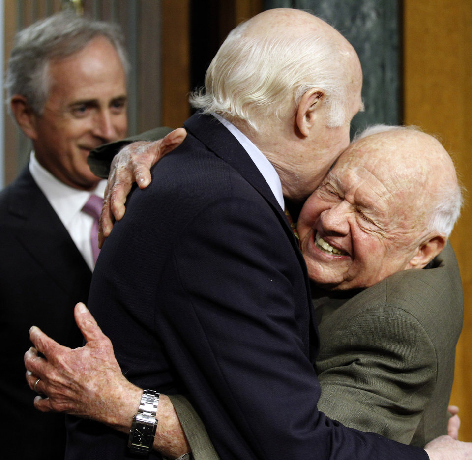 Photo - FILE - In this Wednesday, March 2, 2011, file photo, Senate Aging Committee Chairman Sen. Herb Kohl. D-Wis., center, gets a hug from entertainer Mickey Rooney, right, on Capitol Hill in Washington, as Sen. Bob Corker, R-Tenn., looks on at left, prior to Rooney testifying about elder abuse, before the committee. Rooney, a Hollywood legend whose career spanned more than 80 years, has died. He was 93. Los Angeles Police Commander Andrew Smith said that Rooney was with his family when he died Sunday, April 6, 2014, at his North Hollywood home. (AP Photo/Alex Brandon, File)