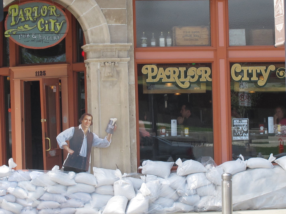 Photo - FILE - In this May 31, 2013, file photo, sandbags are piled around the Parlor City Pub and Eatery in Cedar Rapids, Iowa, where workers placed a cardboard cutout of a man drinking beer. Congress is on the cusp of passing its first infrastructure bill of the year. The Senate is expected to vote Thursday, May 22, 2014, on a $12.3 billion water resources bill that authorizes 34 water projects, from managing flood risks in Cedar Rapids, Iowa, and environmental restoration in Louisiana to dredging Boston Harbor.  (AP Photo/Ryan J. Foley, File)