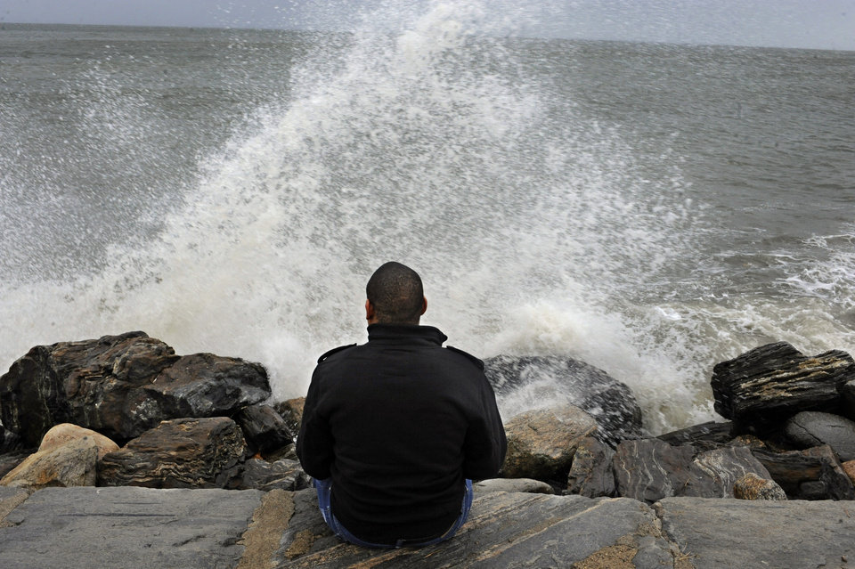 Lamar Chambers watches waves as winds from hurricane Sandy reach Seaside Park in Bridgeport, Conn., Monday, Oct. 29, 2012. Hurricane Sandy continued on its path Monday, forcing the shutdown of mass transit, schools and financial markets, sending coastal residents fleeing, and threatening a dangerous mix of high winds and soaking rain.  (AP Photo/Jessica Hill) ORG XMIT: CTJH101
