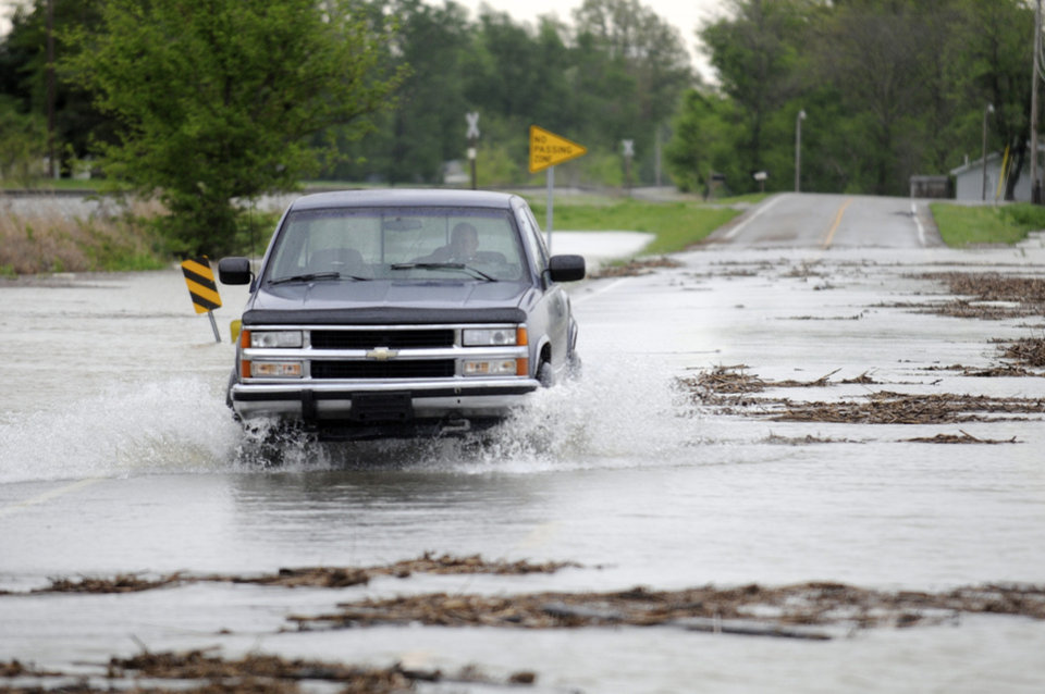 Photo - A man crosses flood waters in his truck on Highway 60 East near Reed, Ky. Wednesday morning, April 27, 2011. Highway 60 was flooded in several places along its route in East Henderson County. (AP Photo/The Gleaner, Darrin Phegley)