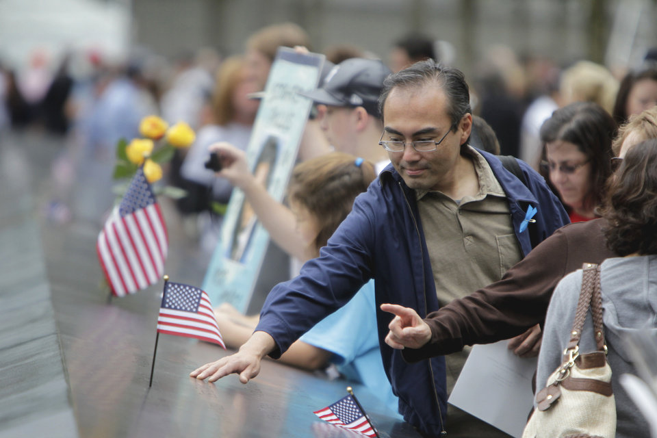 Members of the public run their hands along and make photos of some of the names inscribed on the wall of the Sept. 11 memorial, Sunday, September 11, 2011 in New York. Sunday marked the 10th anniversary of the terrorist attacks on the World Trade Center. (AP Photo/Seth Wenig, Pool)