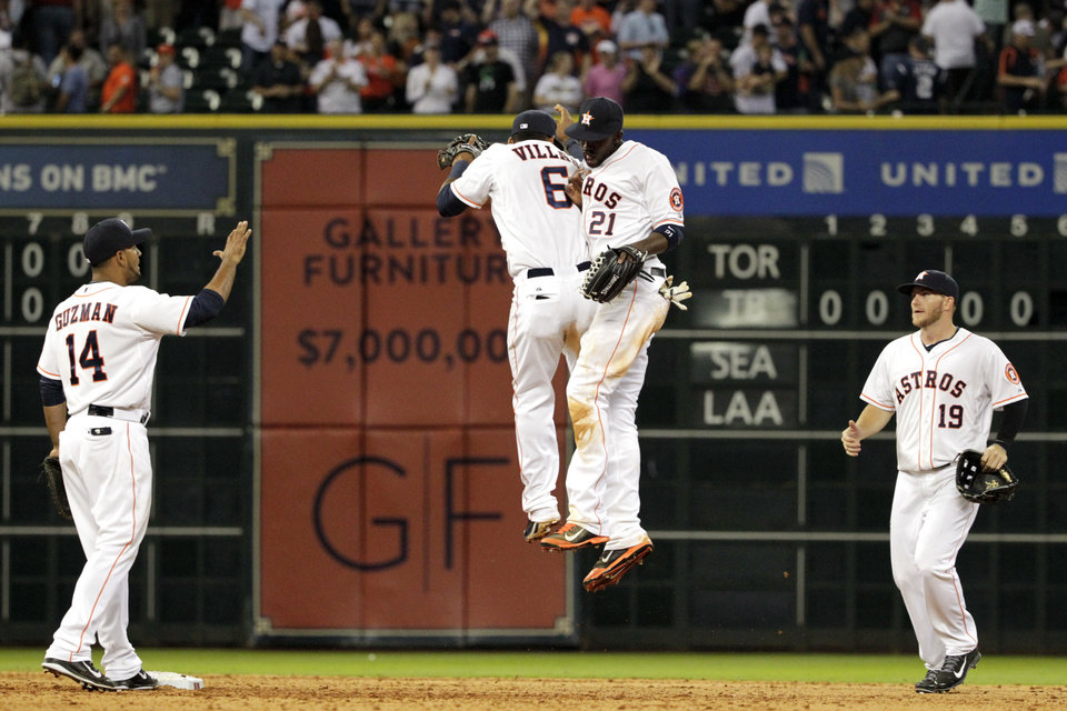 Photo - Houston Astros' Jesus Guzman (14), Jonathan Villar (6), Dexter Fowler (21) and Robbie Grossman (19) celebrate a 6-2 victory over the New York Yankees in a baseball game, Tuesday, April 1, 2014, in Houston. (AP Photo/Patric Schneider)
