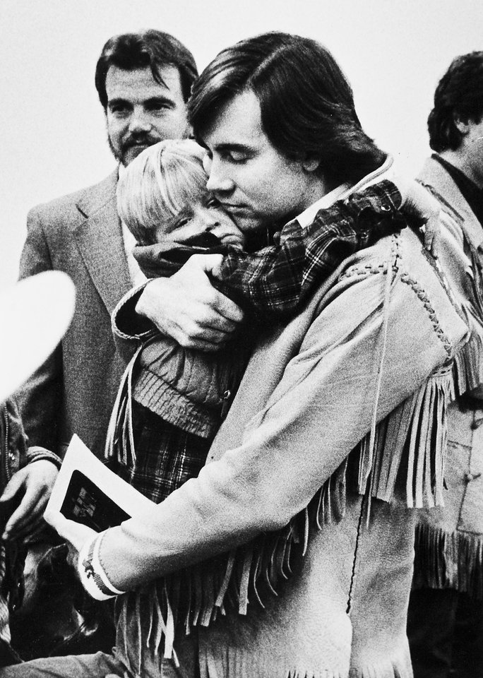Photo - FILE - this 1988 file photo shows Addam Swapp hugging one of his sons during a court hearing in Salt Lake City.  Swapp, the man who bombed a Mormon church building and sparked a 13-day standoff in 1988 that left a corrections officer dead at a polygamist compound, was released from prison on Tuesday, July 9, 2013,  after more than 25 years behind bars.  Swapp, 52, was accompanied by family members as he left Sanpete County Jail three months after members of the state board of pardons and parole approved his release, saying he had shown remorse for leading the standoff in Marion.  (AP Photo/The Salt Lake Tribune, file)