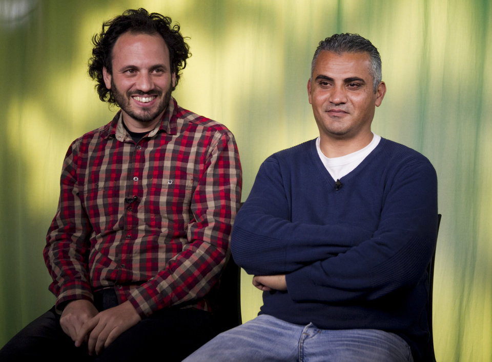 "Photo - In this Tues., Feb. 5, 2013 photo, documentary film Co-directors, Israeli, Guy Davidi, left, and Palestinian, Emad Burnat, pose for a photo after an interview in Los Angeles. Their 2011 documentary film, ""5 Broken Cameras,"" is nominated for an Oscar in the best Documentary Feature category.  (AP Photo/Damian Dovarganes)"