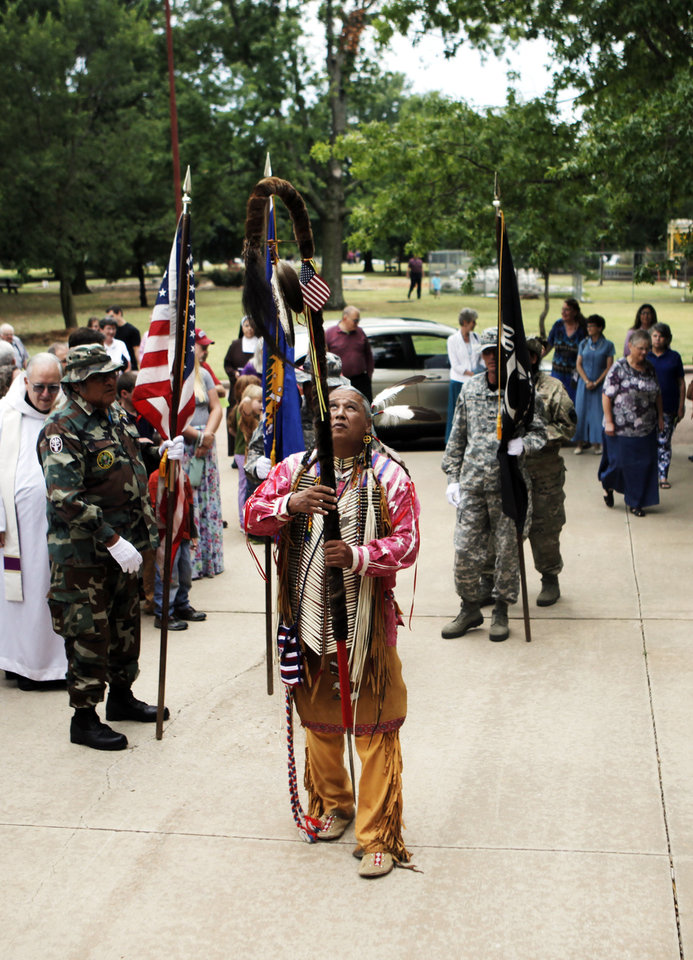 Photo - Albert GrayEagle leads the Shawnee color guard in a procession to the front of the Abbey Church at St. Gregory's Abbey in Shawnee on July 14, 2013 for the celebration of a feast day for Saint Kateri Tekakwitha. Tekakwitha is the first native American canonized by the Roman Catholic church in October 2012. Photo by KT KING, The Oklahoman
