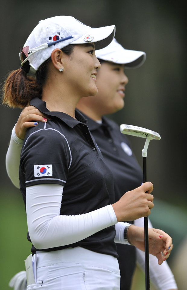 Photo - Inbee Park, right, and So Yeon Ryu, of South Korea, walk to the third hole after putting on the second hole during the first round of the International Crown LPGA golf tournament Thursday, July 24, 2014, in Baltimore.(AP Photo/Gail Burton)