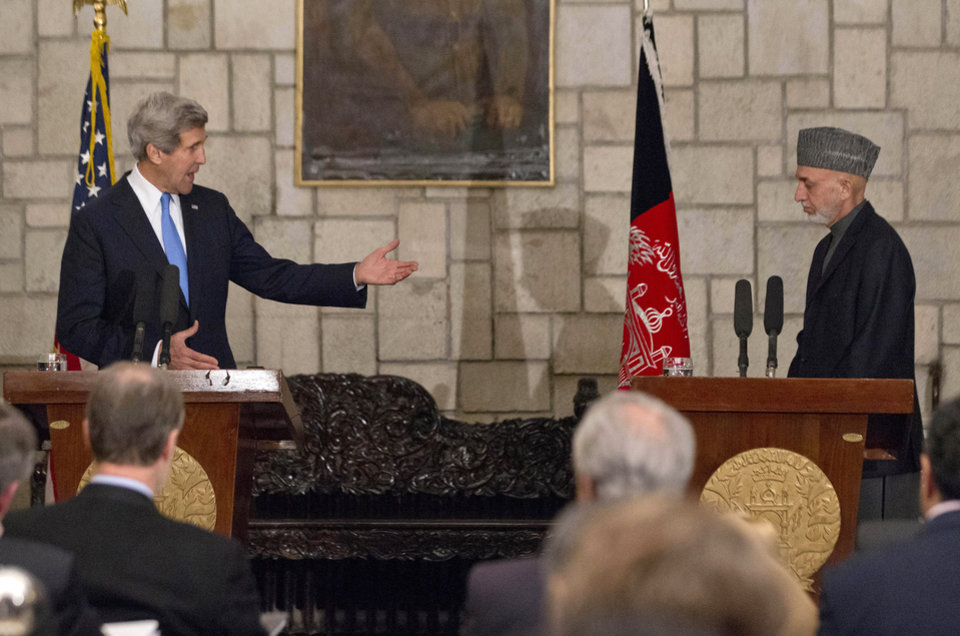 Photo - Secretary of State John Kerry gestures towards Afghan President Hamid Karzai during their joint news conference at the Presidential Palace in Kabul, Monday, March 25, 2013. Kerry and Karzai made a show of unity Monday, shortly after the U.S. military ceded control of its last detention facility in Afghanistan, ending a longstanding irritant in relations between the two countries. Kerry, in Afghanistan for an unannounced visit, said he and Karzai were