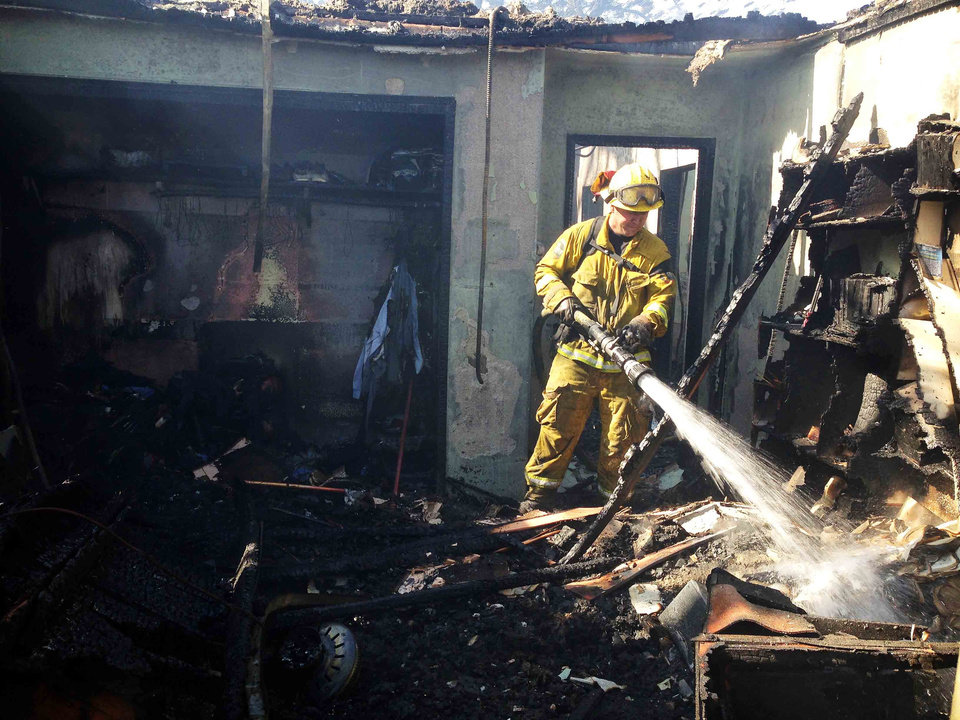 A firefighter puts out the remaining hot spots in the one building that has burned as a result of a brush fire burning in the hills above Banning, Calif., on Wednesday, May 1, 2013. (AP Photo/The Press-Enterprise, Terry Pierson)