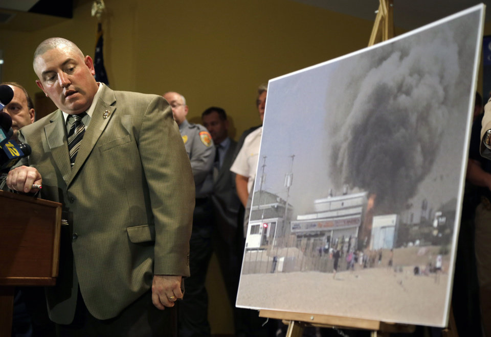 Photo - Ocean County prosecutors office arson investigator Thomas Haskell Jr., uses a laser-pointer on a photograph of a fire that started last Thursday near a frozen custard stand on the boardwalk in Seaside Park, during a news conference in Toms River, N.J., Tuesday, Sept. 17, 2013  Authorities said the massive boardwalk fire was accidental and linked it to electrical wiring and equipment that was compromised by Superstorm Sandy nearly a year ago.  Investigators say the fire, which destroyed more than 50 boardwalk businesses, started under a building that housed a candy store and an ice cream stand. (AP Photo/Mel Evans)