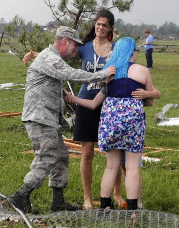 Photo - T. Sgt. Robert Raymond, left, runs to embrace his son Ethan, 11, center partially obscured, with his daughter Lily, 17, right, at Briarwood Elementary school after a tornado destroyed the school in south Oklahoma City on Monday, May 20, 2013.  Paul Hellstern - The Oklahoman