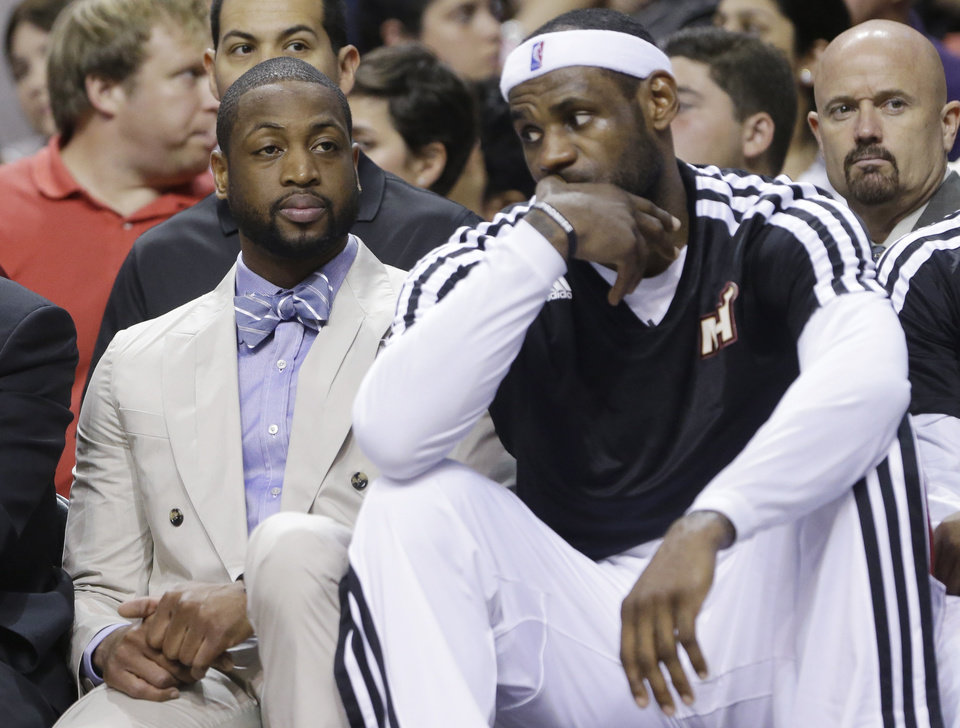 Miami Heat guard Dwyane Wade, left, and forward LeBron James sit on the bench during the first half of an NBA basketball game against the Portland Trail Blazers, Monday, March 24, 2014 in Miami. (AP Photo/Wilfredo Lee)