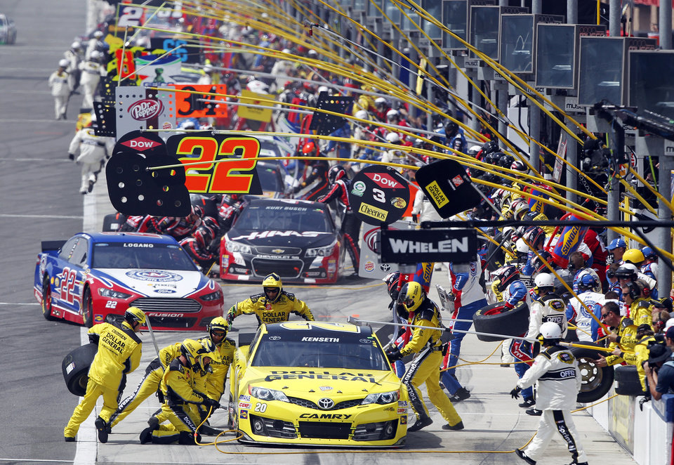 Photo - Pole leader Matt Kenseth (20) leads the pack in the first pit stop in the NASCAR Sprint Series auto race in Fontana, Calif., Sunday, March 23, 2014. (AP Photo/Alex Gallardo)