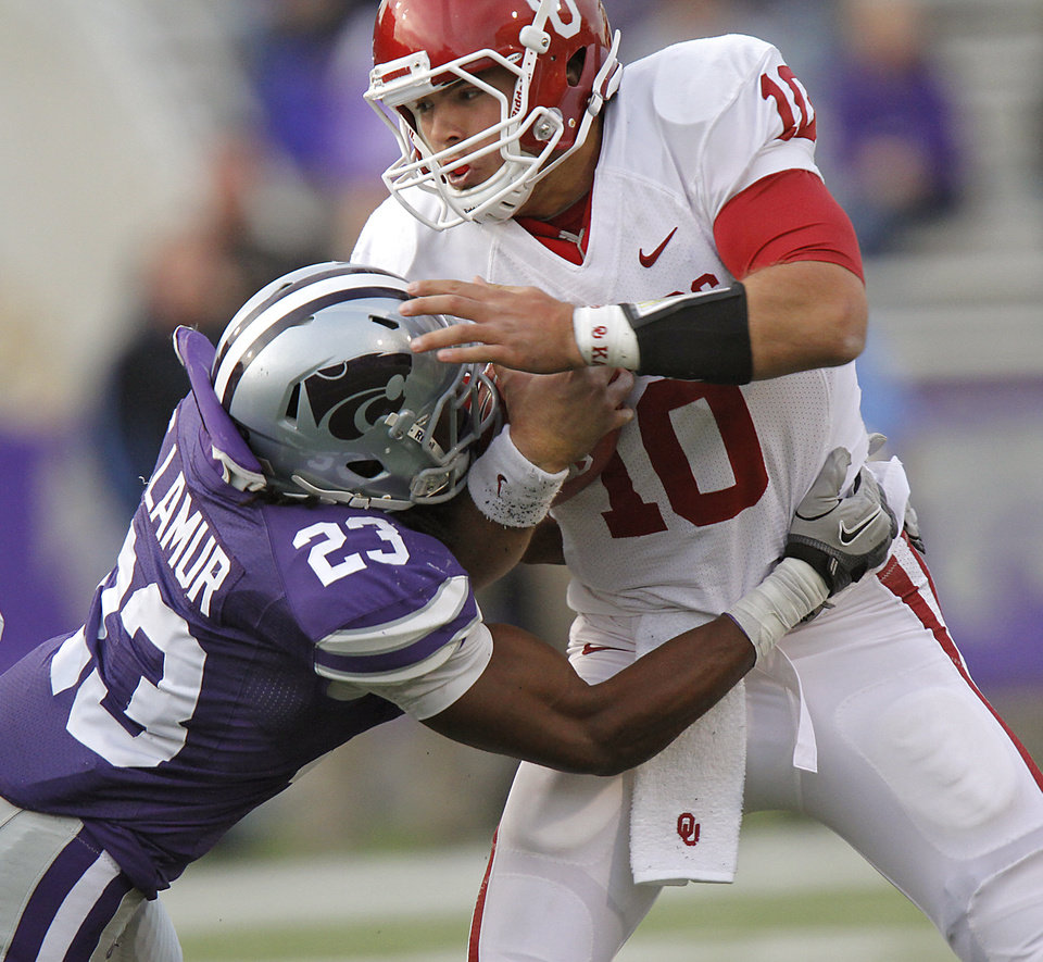Photo - Oklahoma Sooners' Blake Bell (10) is hit by Kansas State Wildcats' Emmanuel Lamur (23) during the college football game between the University of Oklahoma Sooners (OU) and the Kansas State University Wildcats (KSU) at Bill Snyder Family Stadium on Saturday, Oct. 29, 2011. in Manhattan, Kan. Photo by Chris Landsberger, The Oklahoman  ORG XMIT: KOD
