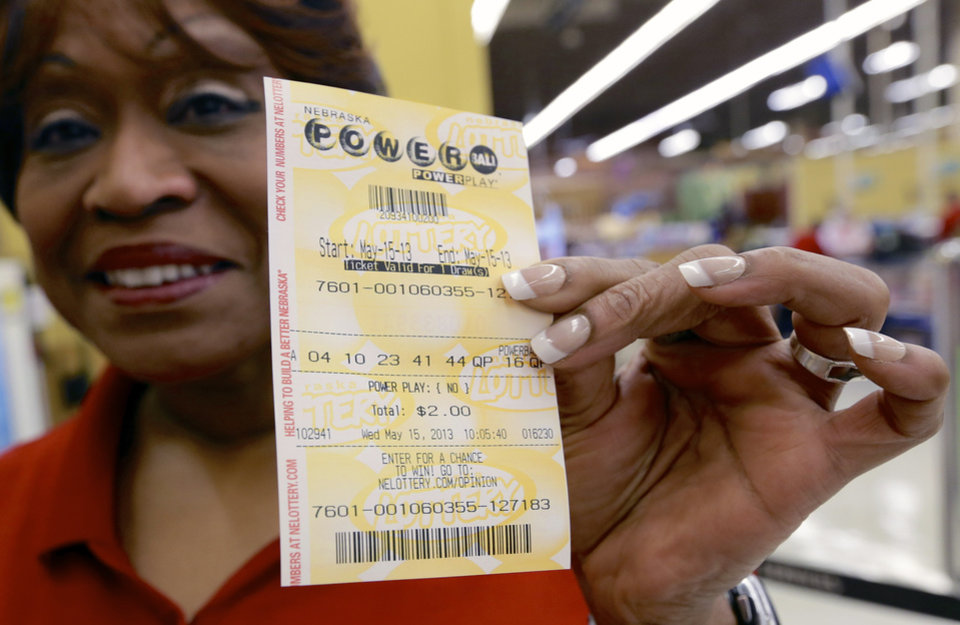 Photo - FILE - In this May 15, 2013, file photo Dean Davis displays the Powerball ticket she bought in Omaha, Neb., Wednesday, May 15, 2013.  No one matched the winning numbers in Wednesday's $360 million jackpot which has now soared to $475 million, making it the second largest in Powerball history and the third biggest overall. The next drawing will be held Saturday. (AP Photo/Nati Harnik)